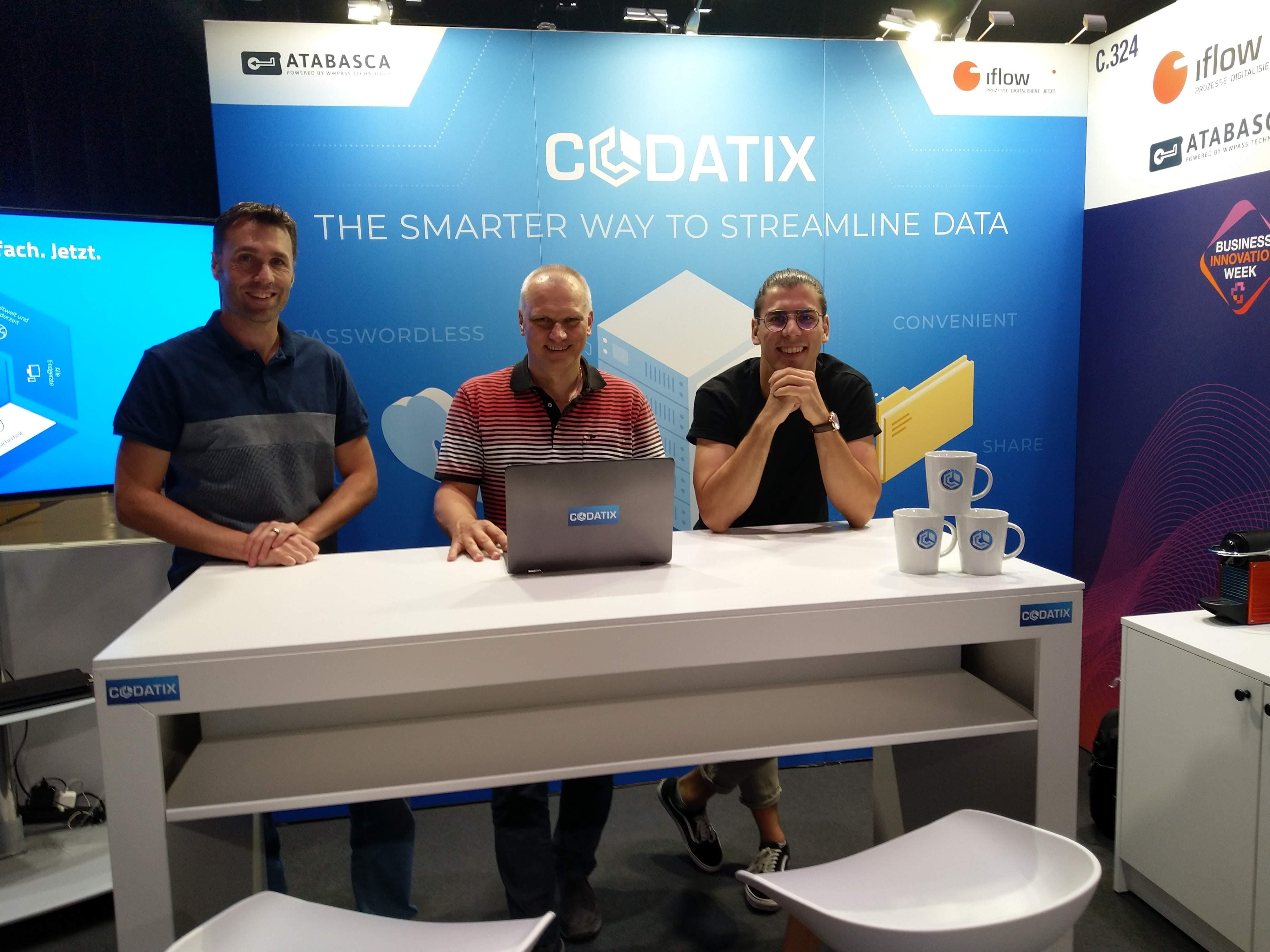 3 Männer stehen hinter einem grossen Tisch vor einem Laptop.
